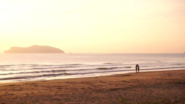 Silhouette di coppia a piedi sulla spiaggia.