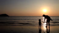 Silhouette daughter with mom playing and relaxing on beach