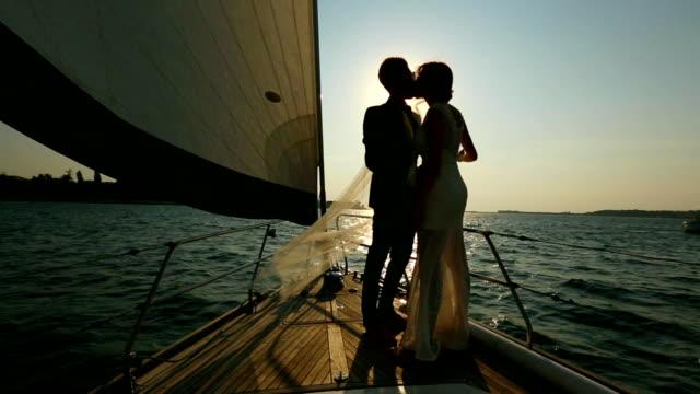 silhouette della sposa e lo sposo baciare la su uno yacht
