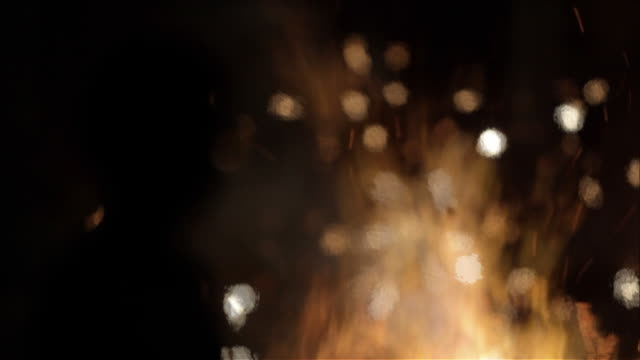 M/S silhouette of a child; fire, petards and sparklers in background, out of focus