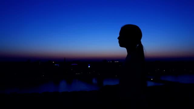 Silhouette der ein Mädchen gegen den Abendhimmel steigen.