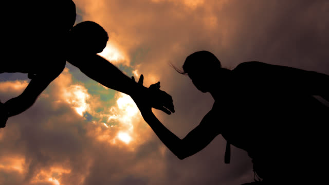 SLO MO silhouette of a helping hand to the woman mountaineer