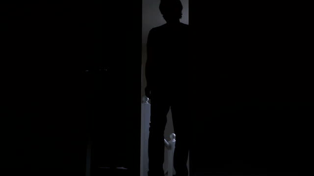 Silhouette of a man entering a dark room.