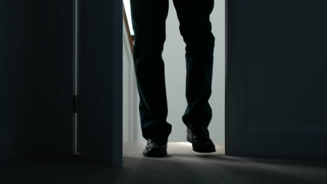 Silhouette of a man opening a door and entering a dark room.