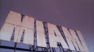 Silhouette of a passenger airplane flying over a large neon Miami sign.