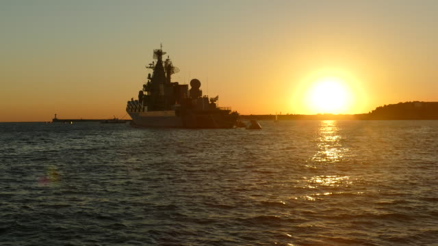 silhouette of a warship at sunset background
