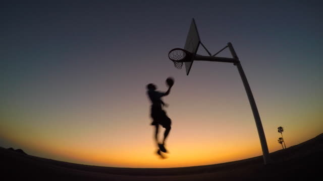 Silhouette of a young man playing street basketball on the beach at sunset.