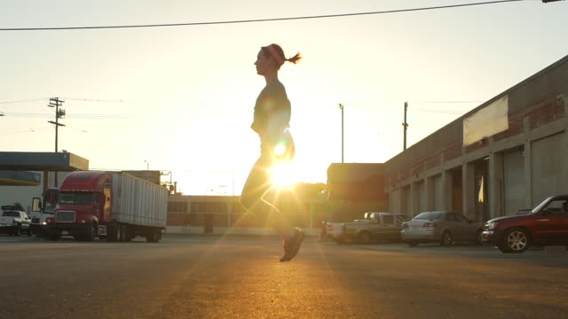 Silhouette of a young woman jump roping in the streets of an urban environment.  - Slow Motion