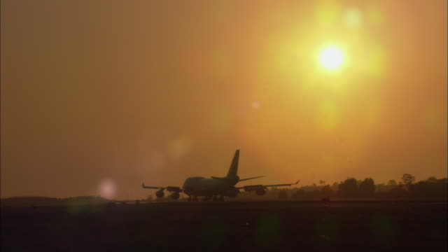 WS, Silhouette of airplane taxiing on tarmac at sunset, Los Angeles International Airport, Los Angeles, California, USA
