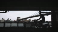 A silhouette of an unrecognizable cyclist riding along NYC's East River in slow motion.