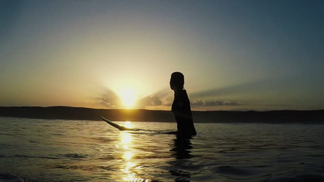 Silhouette of beautiful female surfer at sunrise looking out to sea on surfboard at Atlantic ocean coast in the south of France.