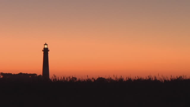 WS, Silhouette of Bodie Island Lighthouse against orange sky at sunset, Nags Head, North Carolina, USA
