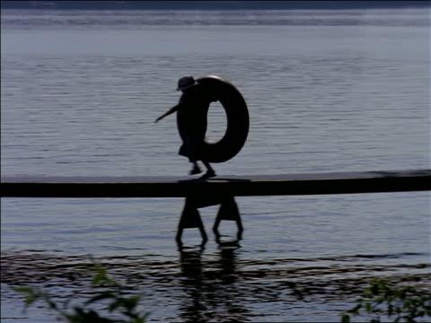 PAN silhouette of boy wearing hat carrying inner tube + running on dock on lake