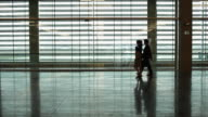 WS Silhouette of businessman and businesswoman crossing airport terminal / Toulouse, Haute-Garonne, France
