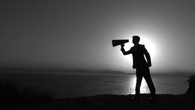 Silhouette Of Businessman Shouting Through Megaphone In Sunset