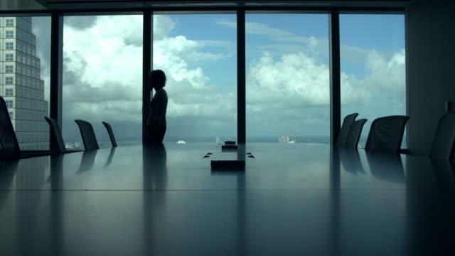 Silhouette der Geschäftsfrau auf Handy im Boardroom