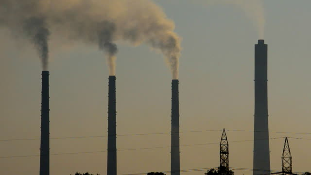 Silhouette of chimneys of power plant releasing smoke in the evening sky