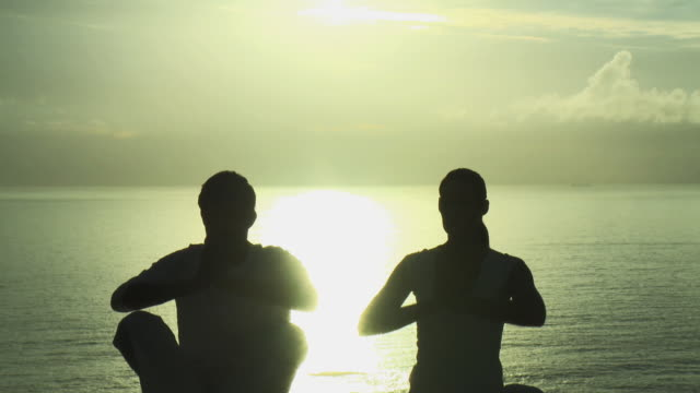 MS Silhouette of couple doing yoga with sea in background / Cape Town, South Africa