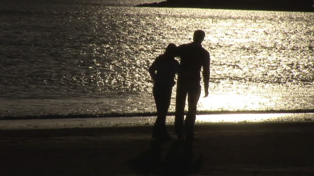 MS, Silhouette of couple embracing on beach at sunset, Kinsale, Ireland