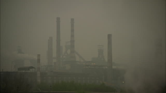 WS Silhouette of factory smokestacks surrounded by thick smog, Beijing, China