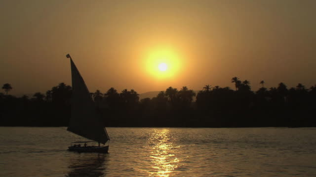 WS Silhouette of felucca sailing on Nile against sun setting over mountains, Aswan, Egypt