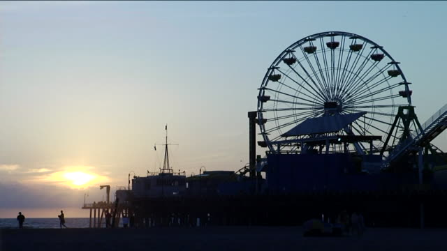 Silhouette of ferris wheel on Santa Monica Pier silhouette of unidentifiable people walking lower frame sun behind some clouds distant BG