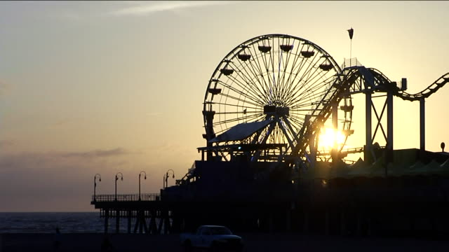 Silhouette of ferris wheel partial roller coaster on Santa Monica Pier BRIGHT orange distant BG CA