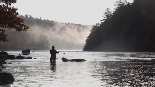 WS PAN Silhouette of fly-fisherman fishing in river / The Forks, Maine, USA