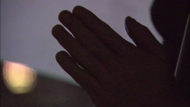 Silhouette of hands and face of a person who is praying under the rain on the 69th Atomicbomb Day of Hiroshima Tilt up