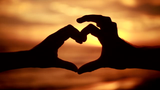 Silhouette of hands on beach at sunset making heart shape