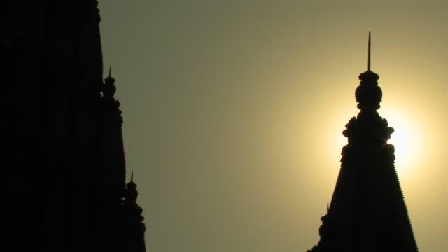 CU, Silhouette of Indian spire building top against golden sky at sunset, Varanasi, Uttar Pradesh, India