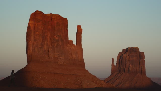 WS, Silhouette of man passing by East Mitten and West Mitten buttes at sunset, Monument Valley, Arizona, USA