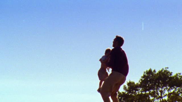 Silhouette of man raising boy in air + spinning around