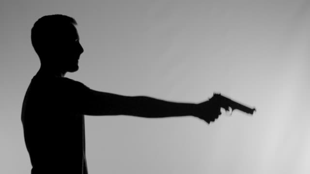 Silhouette of Man Raising Handgun in Super Slow Motion