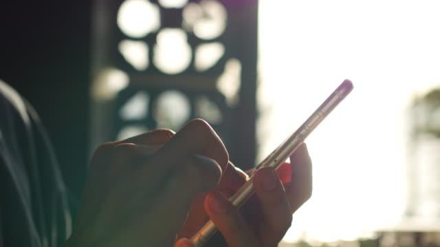 Silhuetten av mannens händer med smart telefon vid solnedgången
