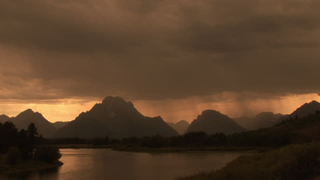WS, Silhouette of mountain range and Snake river in rain at sunset, Grand Teton National Park, Wyoming, USA