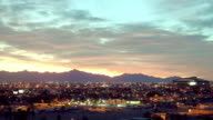 WS T/L ZI Silhouette of mountains behind Phoenix suburbs with Chase Field baseball stadium arena at dusk / Phoenix, Arizona, USA