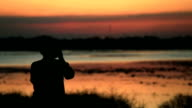 Silhouet van fotograaf tegen zonsondergang, slow-motion