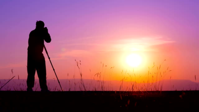 Silhouette of photographer against sunset