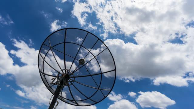 Silhouet van de satellietschotel en wolken in time-lapse