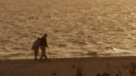 MS, silhouette of senior couple walking on beach / Sanibel, Florida, USA
