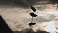 Silhouette of shoes hanging over a telephone line at sunset in Brooklyn, NYC