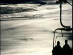 Silhouette of skiers travelling up mountain in ski lift Girdwood Alaska