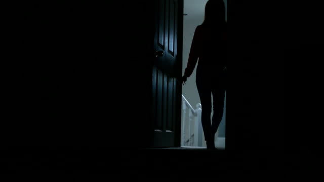 Silhouette of slim young female entering a dark room.