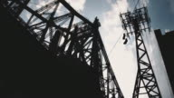 A silhouette of sneakers hanging over a power line in front of NYC's Queensboro Bridge.