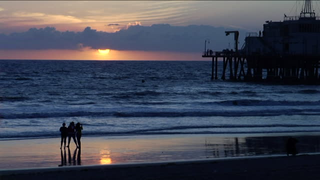 Silhouette of some unidentifiable people on beach lower frame ocean waters silhouette of pier BG sun setting behind clouds above horizon distant BG...