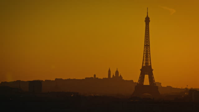 Silhouette of the Eiffel tower and Sacré-Coeur Basilica at sunrise
