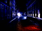 Silhouette of unidentifiable male boxer down empty Plymouth Street shadowboxing in both directions RED LIGHT cast on cobblestone street FG mist BG...