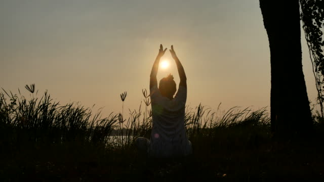 silhouette of woman playing yoga