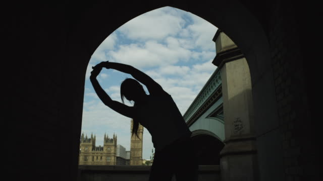 MS Silhouette of woman stretching, Westminster Bridge and Palace of Westminster in background / London, UK